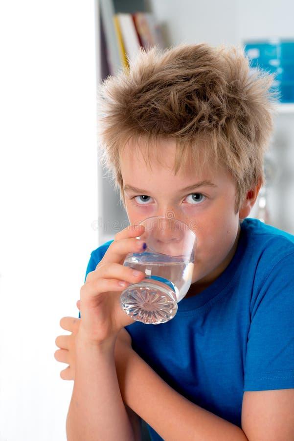 Boy is drinking water. Blond boy is drinking water stock image