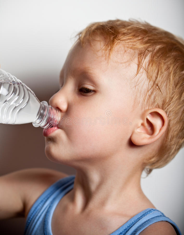 The boy is drinking water from bottle. Quench thirst. The boy is drinking mineral water from plastic bottle royalty free stock photography