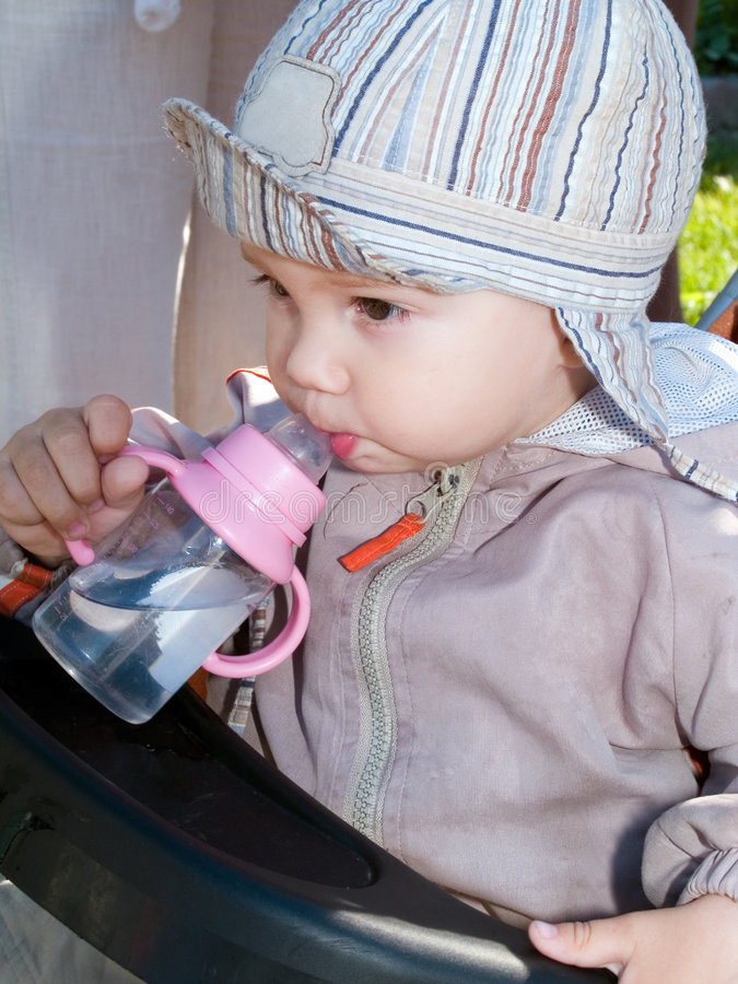 Boy drinking water from bottle stock photography