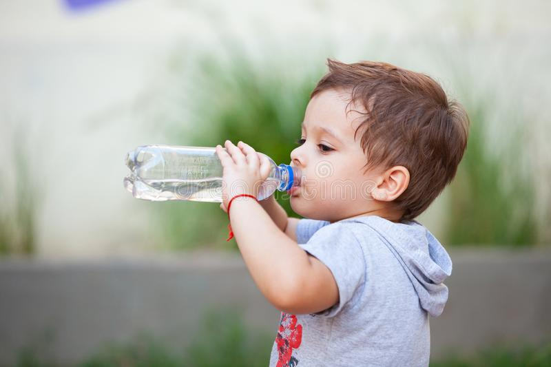 Boy drinking water from a bottle. In park royalty free stock images