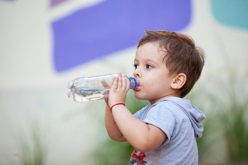 Boy drinking water from a bottle. In park stock image