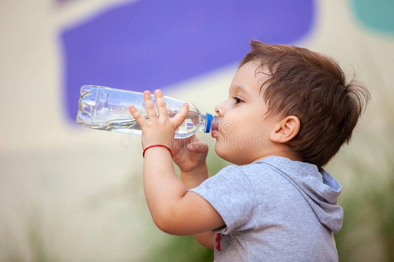 Boy drinking water from a bottle. In park royalty free stock photo