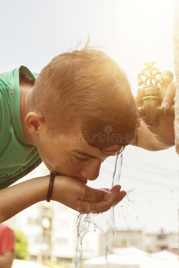 Boy drinking water from oriental tap in the city of prizren royalty free stock photo