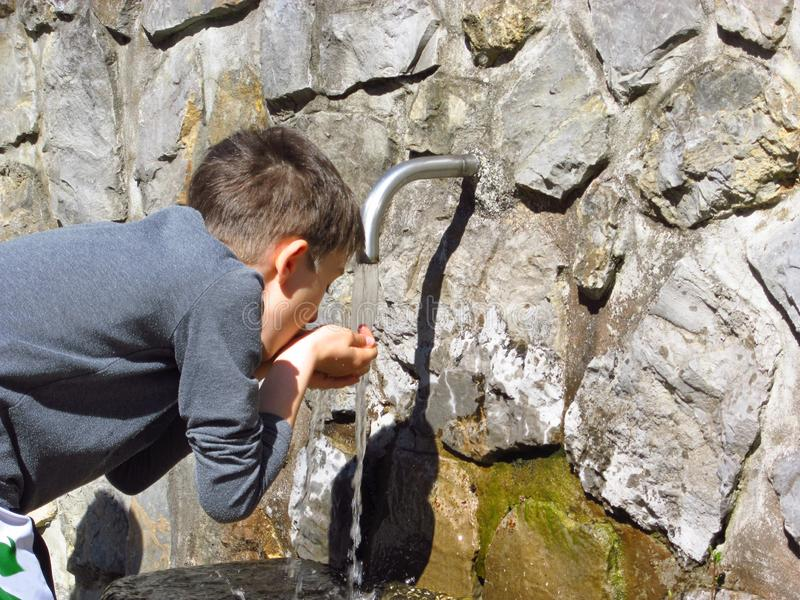 Boy drinking water at spring stock photos