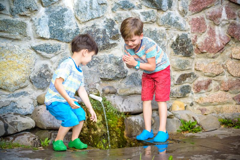 The boy drinks cold water outdoors from the pipe. Two boys brother drinks cold clean water outdoors from the pipe spring or well. Healthy nutrition luted nature royalty free stock images
