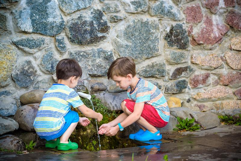 The boy drinks cold water outdoors from the pipe. Two boys brother drinks cold clean water outdoors from the pipe spring or well. Healthy nutrition luted nature royalty free stock photos
