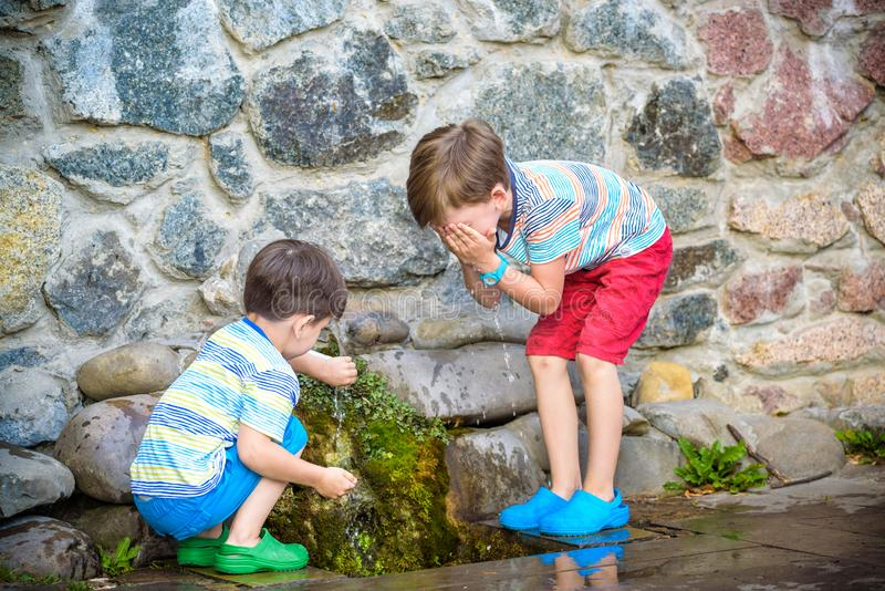 The boy drinks cold water outdoors from the pipe. Two boys brother drinks cold clean water outdoors from the pipe spring or well. Healthy nutrition luted nature stock photo