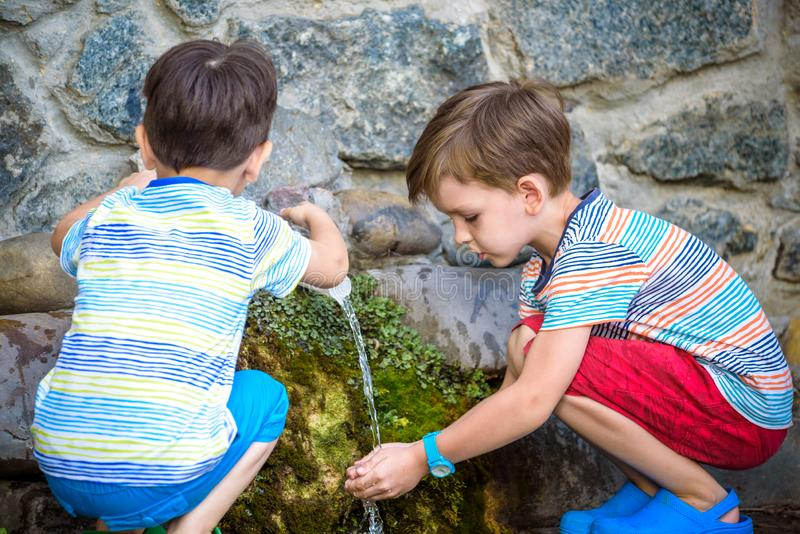 The boy drinks cold water outdoors from the pipe. Two boys brother drinks cold clean water outdoors from the pipe spring or well. Healthy nutrition luted nature royalty free stock image