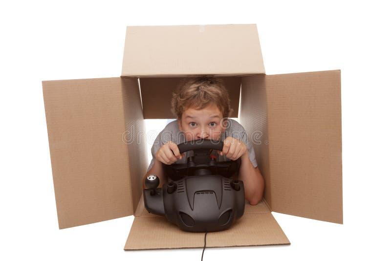 Boy-driver of a cardboard box stock image