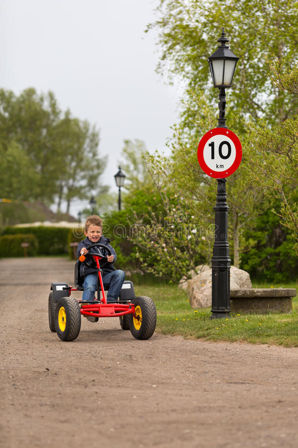 Boy driving buggy cart. Next to 10 MPH speed limit sign. Trademarks have been removed stock image