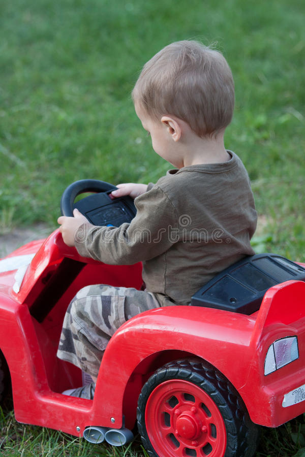 Boy driving toy car royalty free stock photo