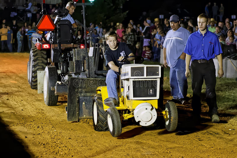 Boy Driving Tractor at Pulling Competition. MYERSTOWN, PENNSYLVANIA - SEPTEMBER 16, 2016: A young boy drives a modified lawn tractor at Myerstown East End Days stock photo