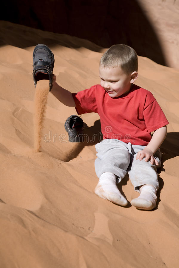 Boy dumping sand out of shoes. A young boy dumping red sand out of his shoes stock photos