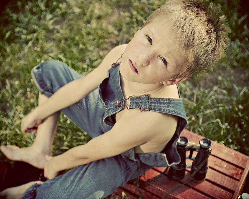 Boy in dungarees. With binoculars stock images