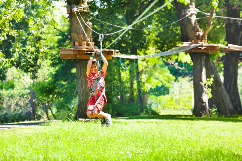 Boy at easy low zip line for kids, adventure park royalty free stock image