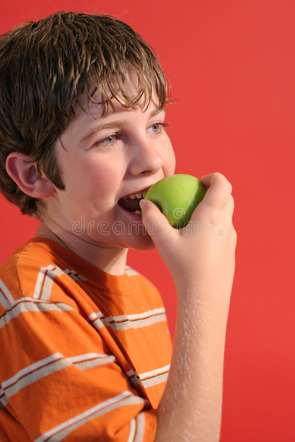Boy eating an apple vertical stock photography