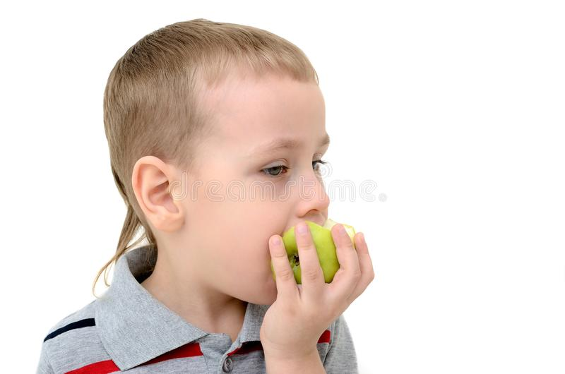 Boy eating an apple on a white background royalty free stock photos