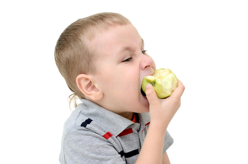 Boy eating an apple on a white background stock photography