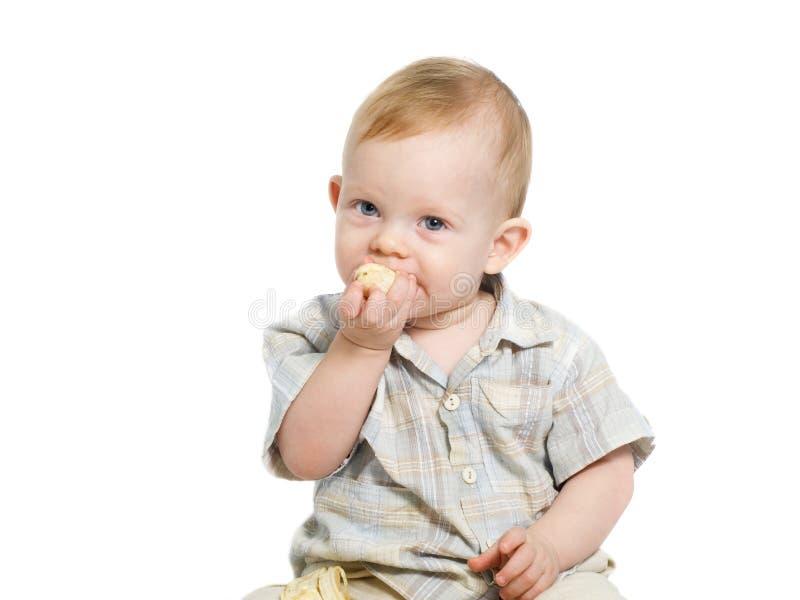 Boy eating babana. 12-month old blue eyed toddler eating a banana stock image