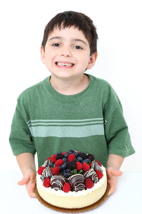 Boy Eating Cheesecake. Adorable six year old boy eating glazed fruit cheesecake royalty free stock photography