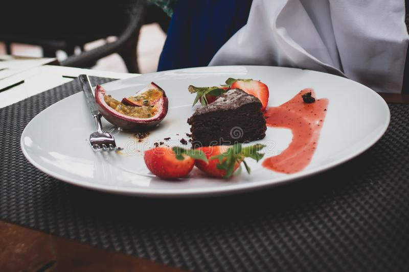 Boy eating chocolate brownie and berries. stock images