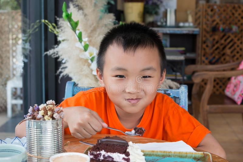 Boy eating chocolate cakes. In coffee shop royalty free stock images