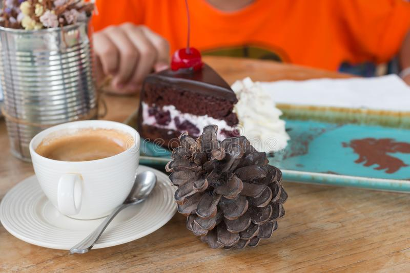 Boy eating chocolate cakes. In coffee shop royalty free stock photo