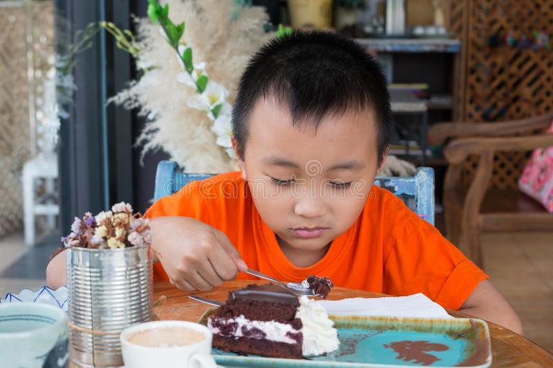 Boy eating chocolate cakes. In coffee shop royalty free stock image