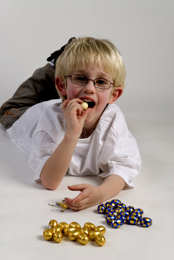 Boy is eating chocolate egg. S from easter royalty free stock image
