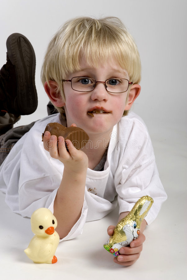 Boy is eating chocolate hare. From easter royalty free stock photography