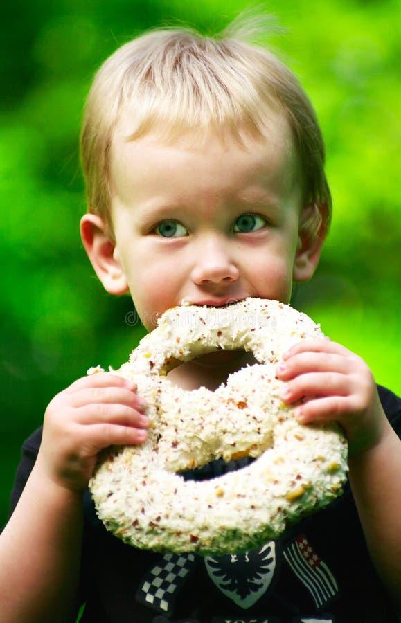 Boy eating a chocolate pretzel royalty free stock photo