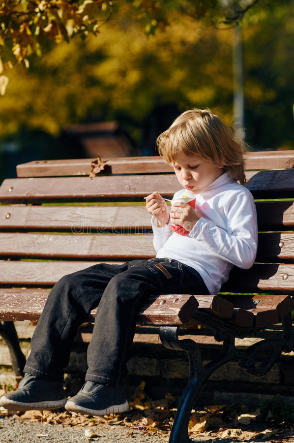 Boy Eating a corn on bench. Child boy eating corn from cup. National Foods in Bulgaria stock photo