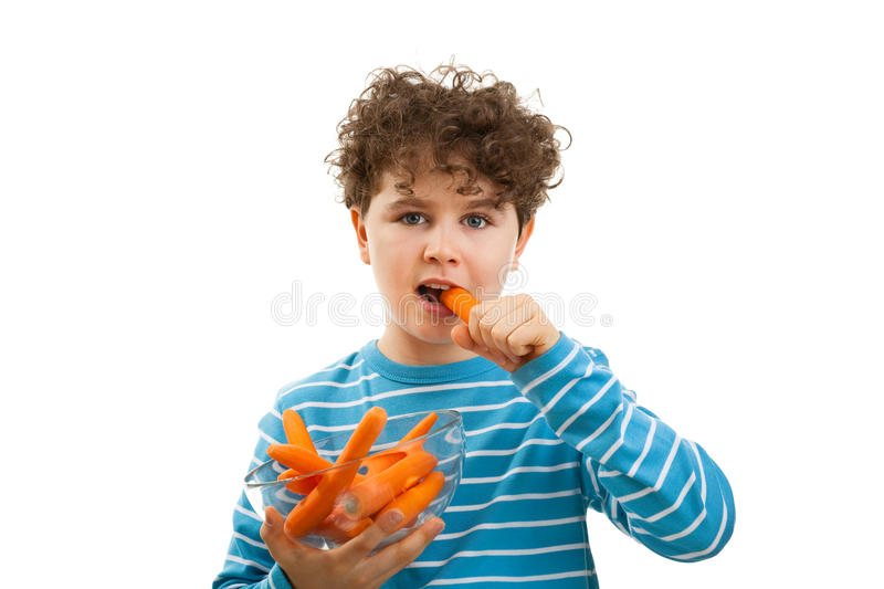 Boy eating fresh carrot. Isolated on white background stock photos