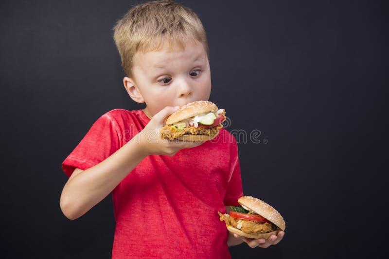 Boy eating a hamburger stock photo