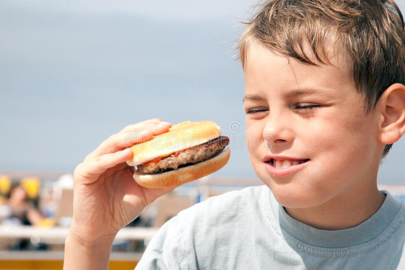Boy eating hamburger on ship