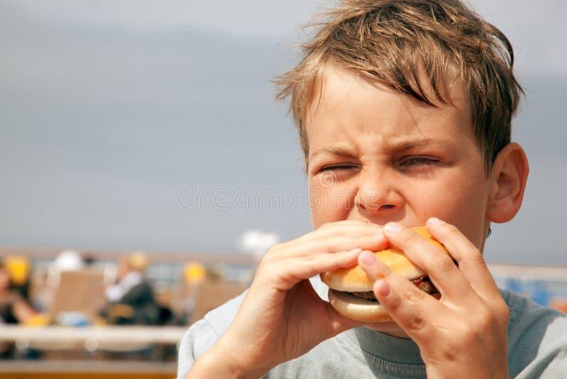 Boy eating hamburger on ship