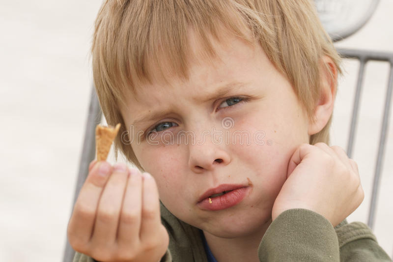 Boy eating ice cream, who present disappointment because of that I ate it asks for the next royalty free stock photography