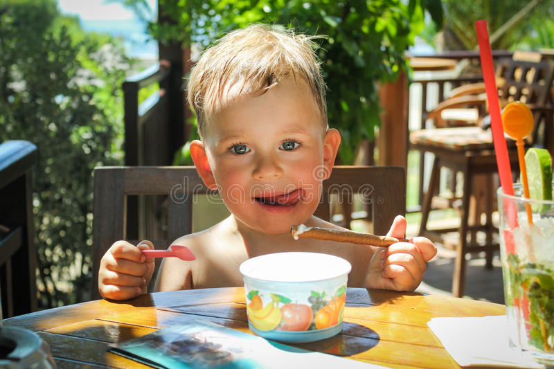Boy eating ice cream. Portrait of child with ice cream and waffle roll in summertime royalty free stock image