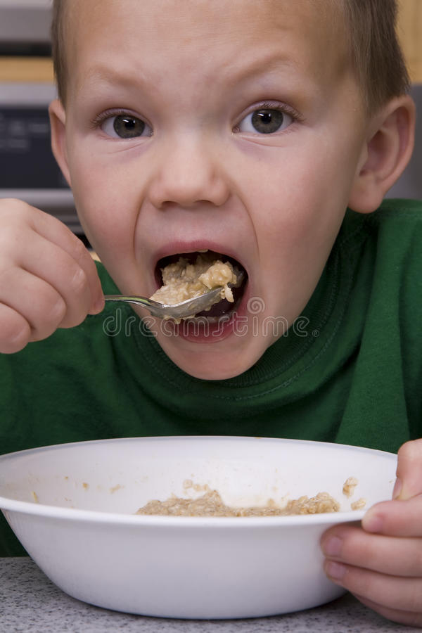 Boy eating oatmeal big bite. Young boy eating oatmeal for breakfast taking a big bite royalty free stock image