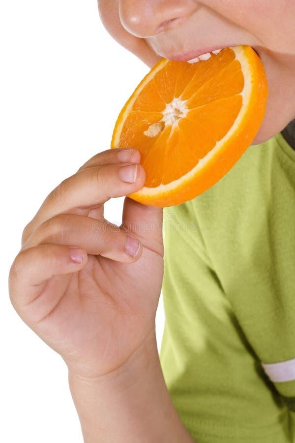 Boy eating orange slice - closeup royalty free stock photos