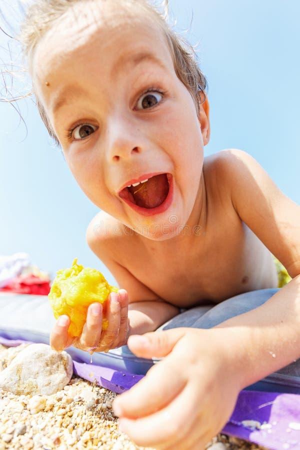 Boy eating a peach. Cute boy eating a peach on the beach royalty free stock images