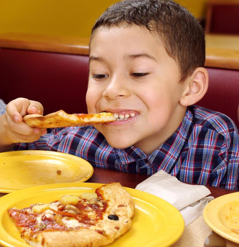 Boy eating a pizza. Seven year old boy enjoying a slice of pizza in a booth at a pizza restaurant stock images