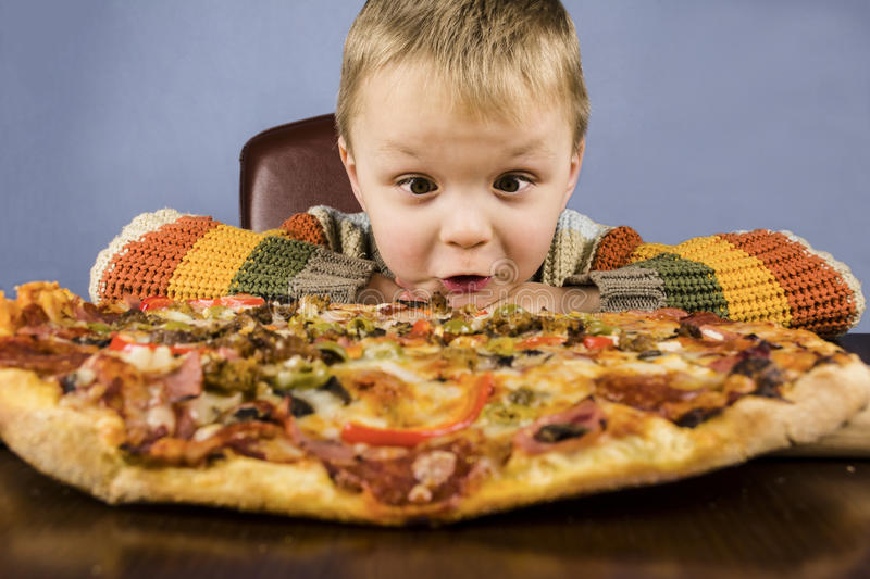 Boy eating pizza royalty free stock photography