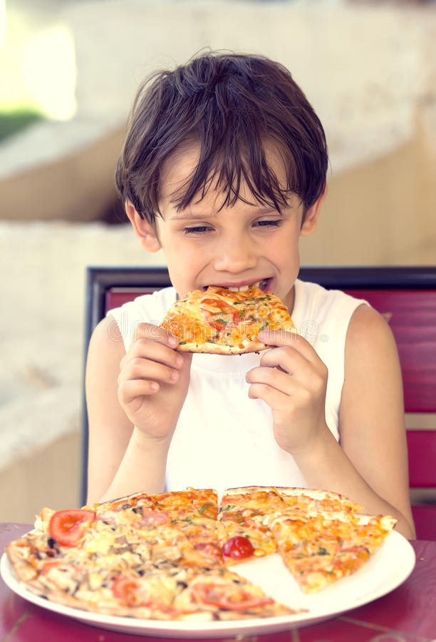 Boy eating pizza royalty free stock images