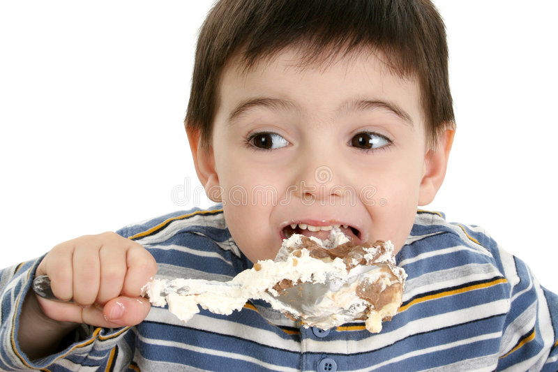 Boy Eating Possum Pie. Close up of a two year old boy eating possum pie with a big silver spoon. Shot in studio over white royalty free stock image