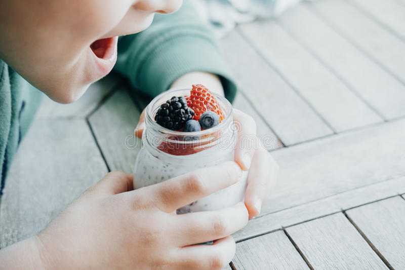 Boy eating Pudding with chia seeds, yogurt and fresh fruits: Strawberries, blueberries and blackberries in glass jars on wooden b stock photo