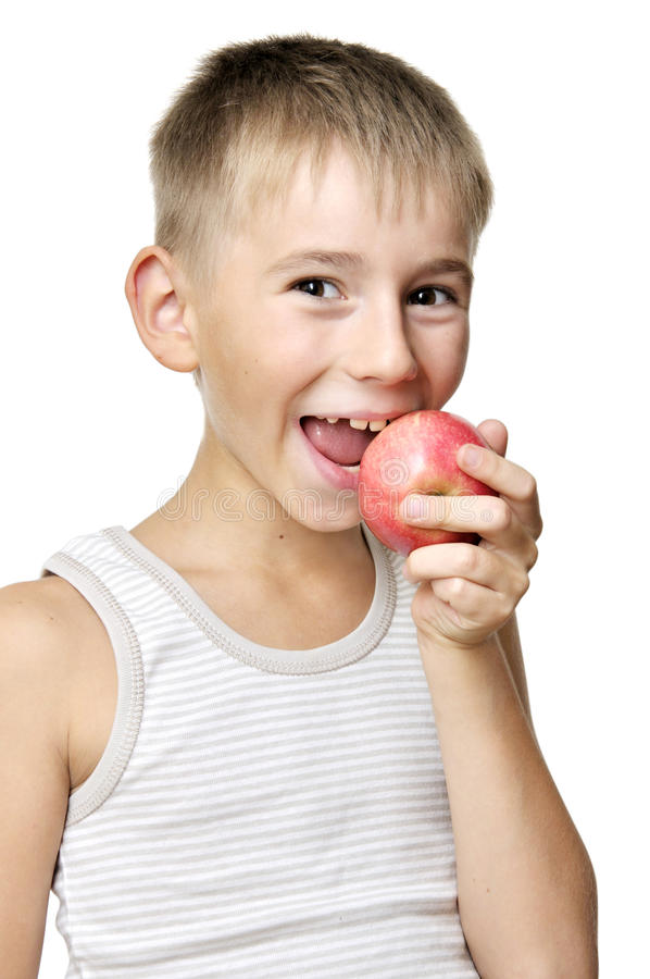 Boy eating red apple. Cute boy eating red apple isolated on a white background royalty free stock photo