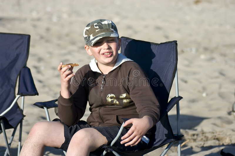 Download Boy Eating Sandwich On Beach Stock Photos - Image: 5143303