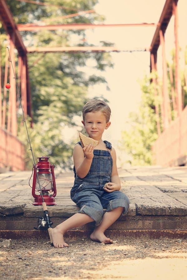Boy eating sandwich taking break from fishing. Boy eating sandwich fishing bridge stock photos
