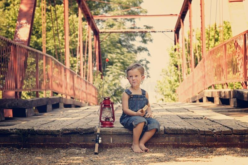 Boy eating sandwich taking break from fishing. Boy eating sandwich fishing bridge stock images